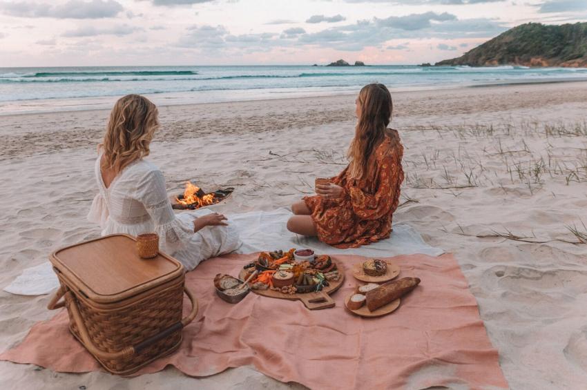 deux filles en train de manger sur la plage autour dun feu