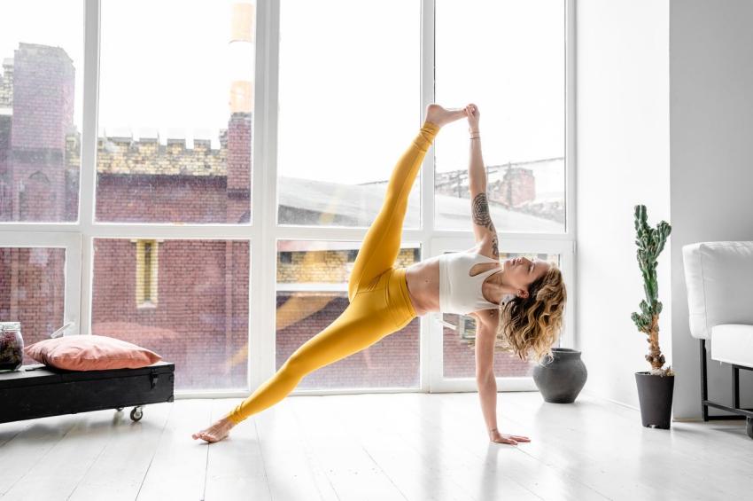 femme qui fait du yoga dans son appartement en face de la fenetre