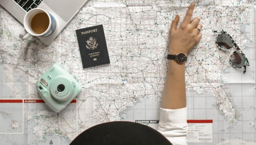 femme qui pointe une destination sur une carte du monde