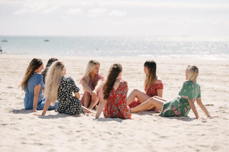 groupe de filles sur la plage formant un cercle et discutant