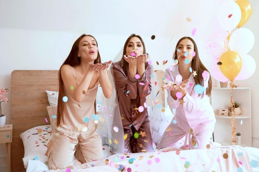 trois filles sur un lit qui souffle sur des confettis